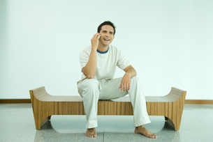 man sitting on bench using cell phoneの写真素材 [FYI04321360]