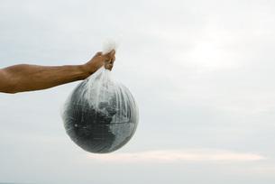 Arm holding globe in plastic bagの写真素材 [FYI04321383]