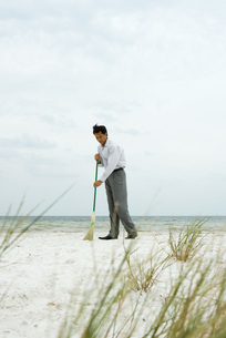 Man standing at the beach sweeping sandの写真素材 [FYI04321387]
