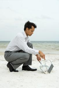 Man crouching & using broom and dustpanの写真素材 [FYI04321394]