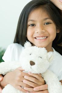 Girl holding teddy bear at cameraの写真素材 [FYI04321471]