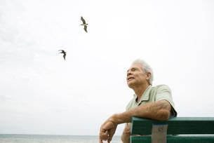 man sitting on bench at beachの写真素材 [FYI04321483]