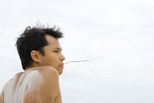 Man holding piece of straw in his mouthの写真素材 [FYI04321485]