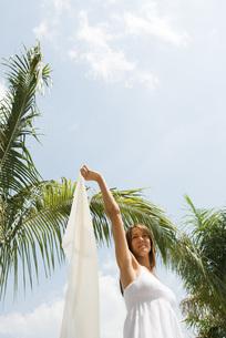 Woman standing under palm treeの写真素材 [FYI04321493]