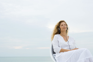 Woman sitting & listening to headphonesの写真素材 [FYI04321500]