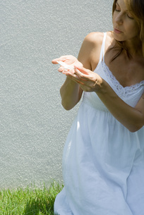 Woman holding butterfly in cupped handsの写真素材 [FYI04321513]