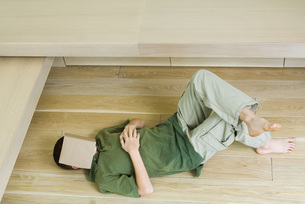 Boy lying on floor with book over faceの写真素材 [FYI04321521]