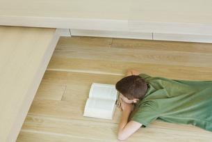Boy lying on floor, reading bookの写真素材 [FYI04321542]