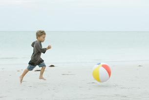 boy running after ball on beachの写真素材 [FYI04321552]