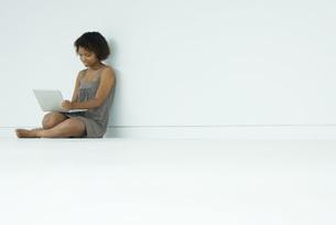 woman sitting on floor, using laptopの写真素材 [FYI04321563]