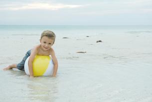 boy lying on beach ball at cameraの写真素材 [FYI04321568]