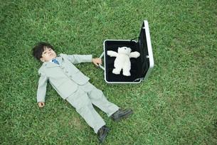 boy in full suit, lying on grassの写真素材 [FYI04321569]