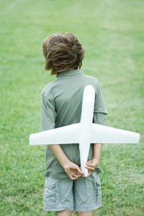 Boy holding toy airplane behind backの写真素材 [FYI04321574]