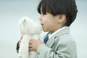boy in suit kissing teddy bearの写真素材 [FYI04321594]