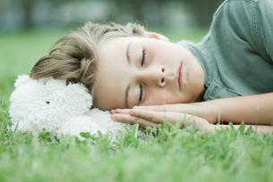 Boy resting head on teddy bearの写真素材 [FYI04321597]