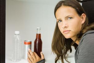 girl reaching for bottled soft drinkの写真素材 [FYI04321602]