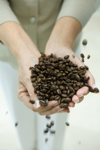 Woman's hands holding coffee beansの写真素材 [FYI04321603]