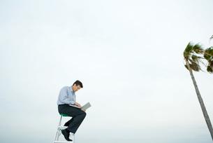 Man sitting in wind, using laptopの写真素材 [FYI04321607]