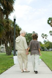 Boy and grandmother walking on sidewalkの写真素材 [FYI04321608]