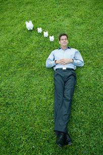 Man lying, piggy banks next to headの写真素材 [FYI04321613]