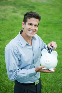 Man putting credit card into piggy bankの写真素材 [FYI04321622]