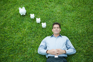 Man lying on grass, piggy banks by headの写真素材 [FYI04321624]