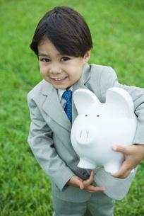 boy holding piggy bank under armの写真素材 [FYI04321629]