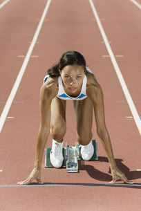 Woman crouched in starting position on running trackの写真素材 [FYI04321634]