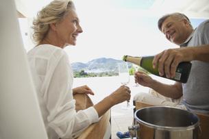 Couple enjoying champagne outdoorsの写真素材 [FYI04321636]