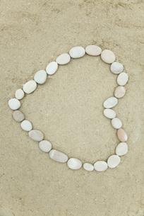 Pebbles arranged in heart shape on sandの写真素材 [FYI04321637]