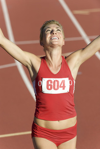Woman running on track with arms raised in victoryの写真素材 [FYI04321638]