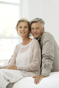 Mature couple sitting together on bed, portraitの写真素材 [FYI04321642]