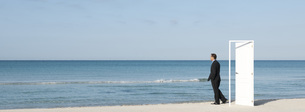 Businessman standing on beach next to half-open door, lookinの写真素材 [FYI04321655]