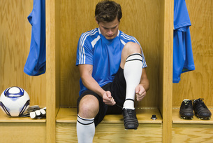 Young soccer player tying shoeの写真素材 [FYI04321660]