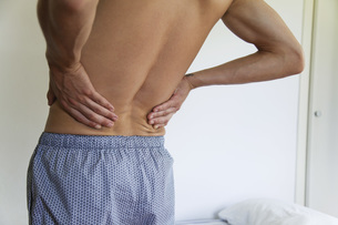 Man experiencing lower back pain, croppedの写真素材 [FYI04321666]