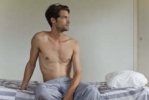 Man sitting on bed, looking away in thoughtの写真素材 [FYI04321674]