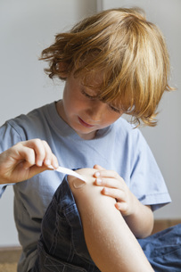 Boy removing adhesive bandage from kneeの写真素材 [FYI04321682]