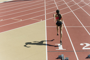 Woman running on track, rear viewの写真素材 [FYI04321687]