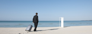 Businessman pulling suitcase on beach, walking towards half-の写真素材 [FYI04321693]