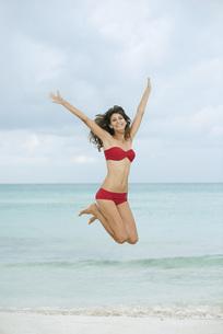 Young woman in bikini jumping in midair at the beachの写真素材 [FYI04321695]