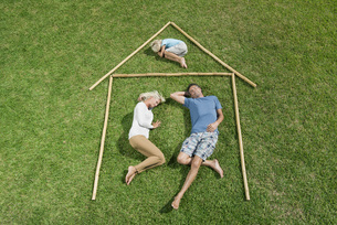 Family with one child lying on grass within outline of houseの写真素材 [FYI04321709]