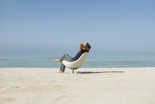 Mid-adult man relaxing in armchair on beachの写真素材 [FYI04321713]