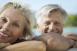 Mature couple resting their heads on side of pool, portraitの写真素材 [FYI04321715]