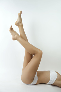 Woman lying on back in underwear with legs in air, croppedの写真素材 [FYI04321722]