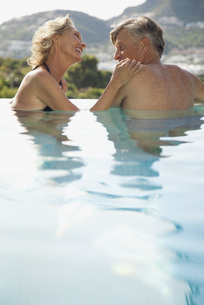 Mature couple relaxing together in poolの写真素材 [FYI04321734]