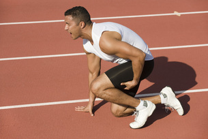 Injured runner kneeling on running trackの写真素材 [FYI04321735]