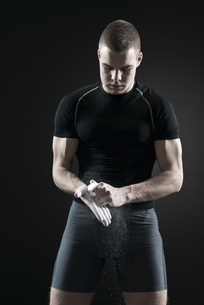 Male athlete applying chalk to handsの写真素材 [FYI04321742]