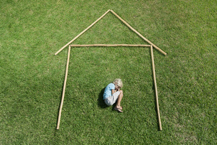 Boy in fetal position within outline of house, high angle viの写真素材 [FYI04321749]