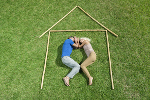 Couple lying on grass within outline of house, high angle viの写真素材 [FYI04321763]