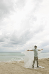 Man trapped in plastic on beachの写真素材 [FYI04321767]